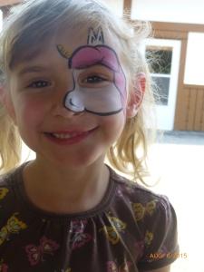 Face painted like a unicorn.